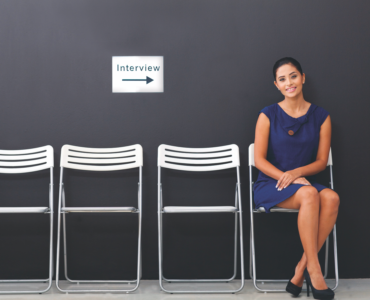 woman sitting in a row of chairs