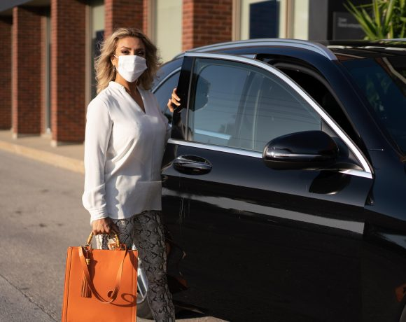 woman getting out of a car with a white mask