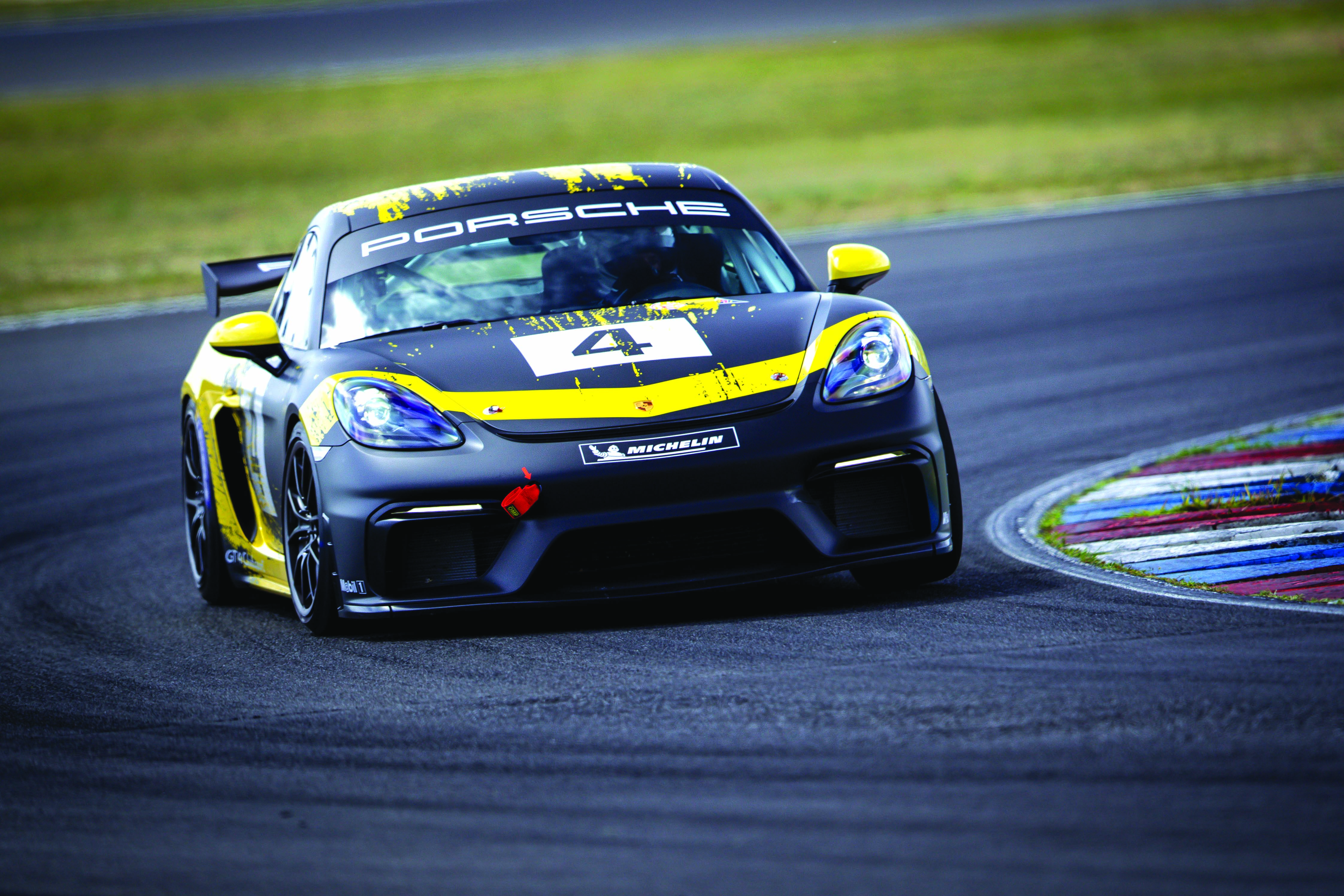 a black and yellow race car racing on the track