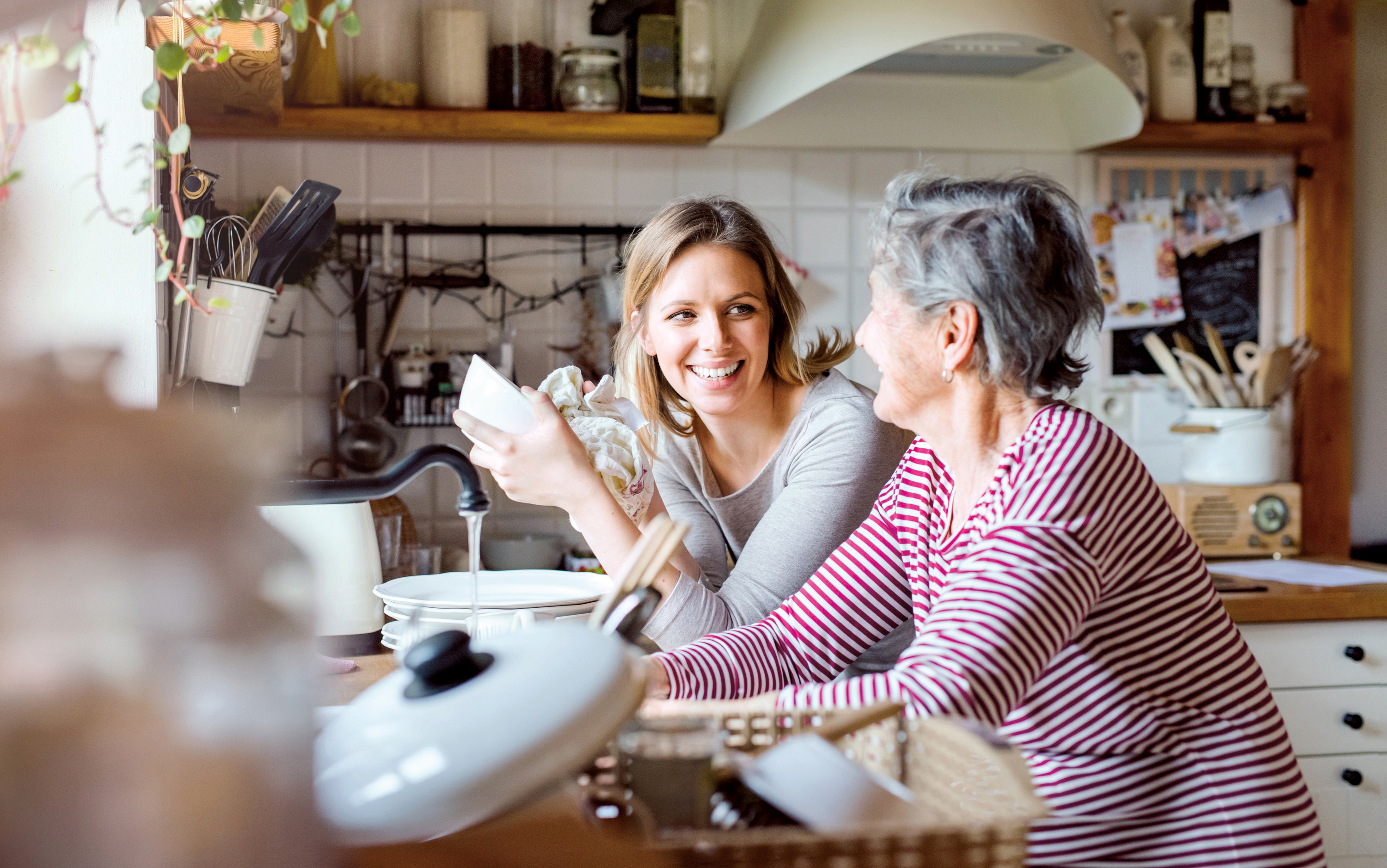 a woman and her mother washing dishes together smiling and laughing