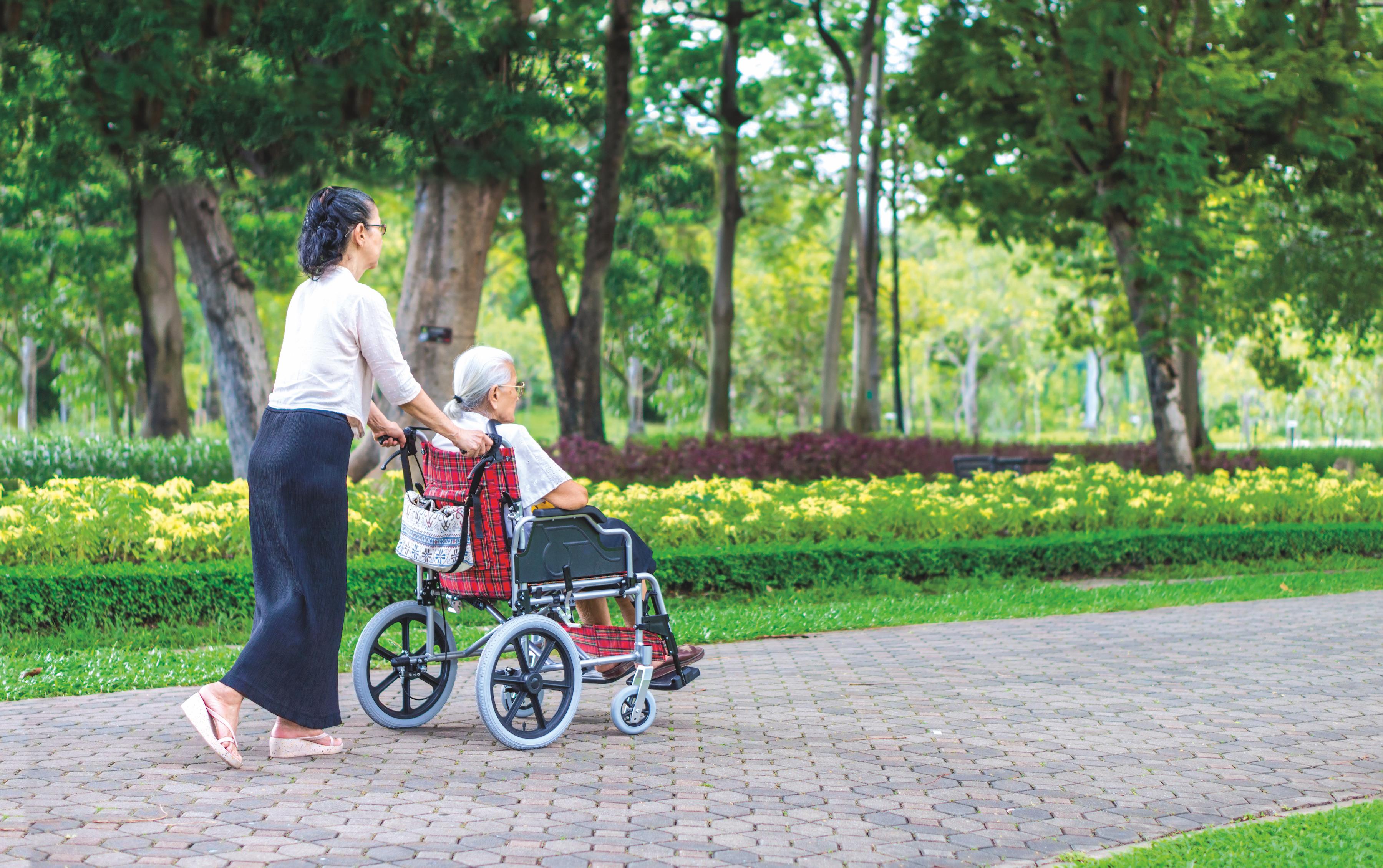 A woman pushing an elderly woman in a wheelchair