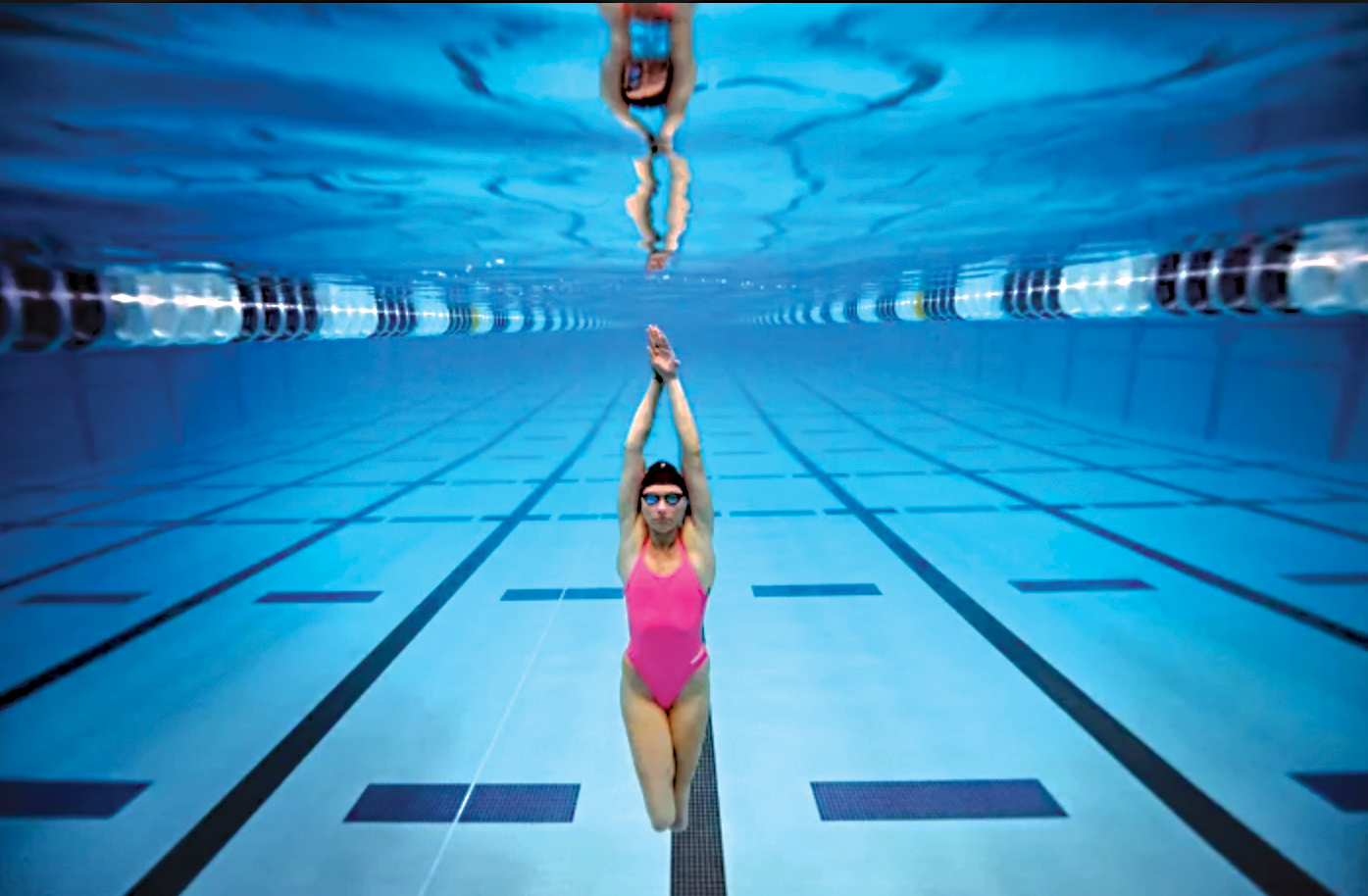 woman swimming in a pink bathing suit in a swimming lane