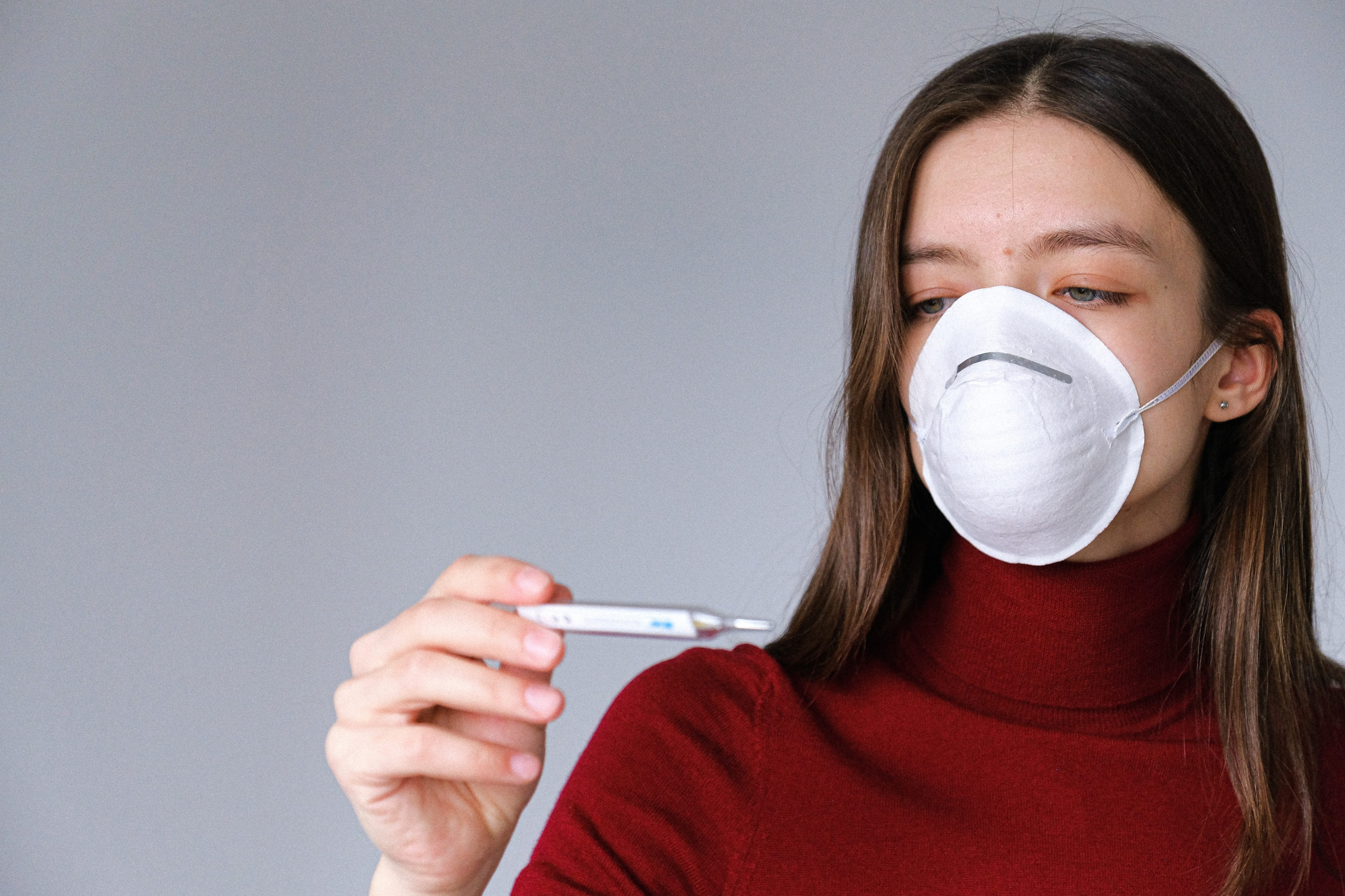woman in a white mask and red shirt looking at a thermometer