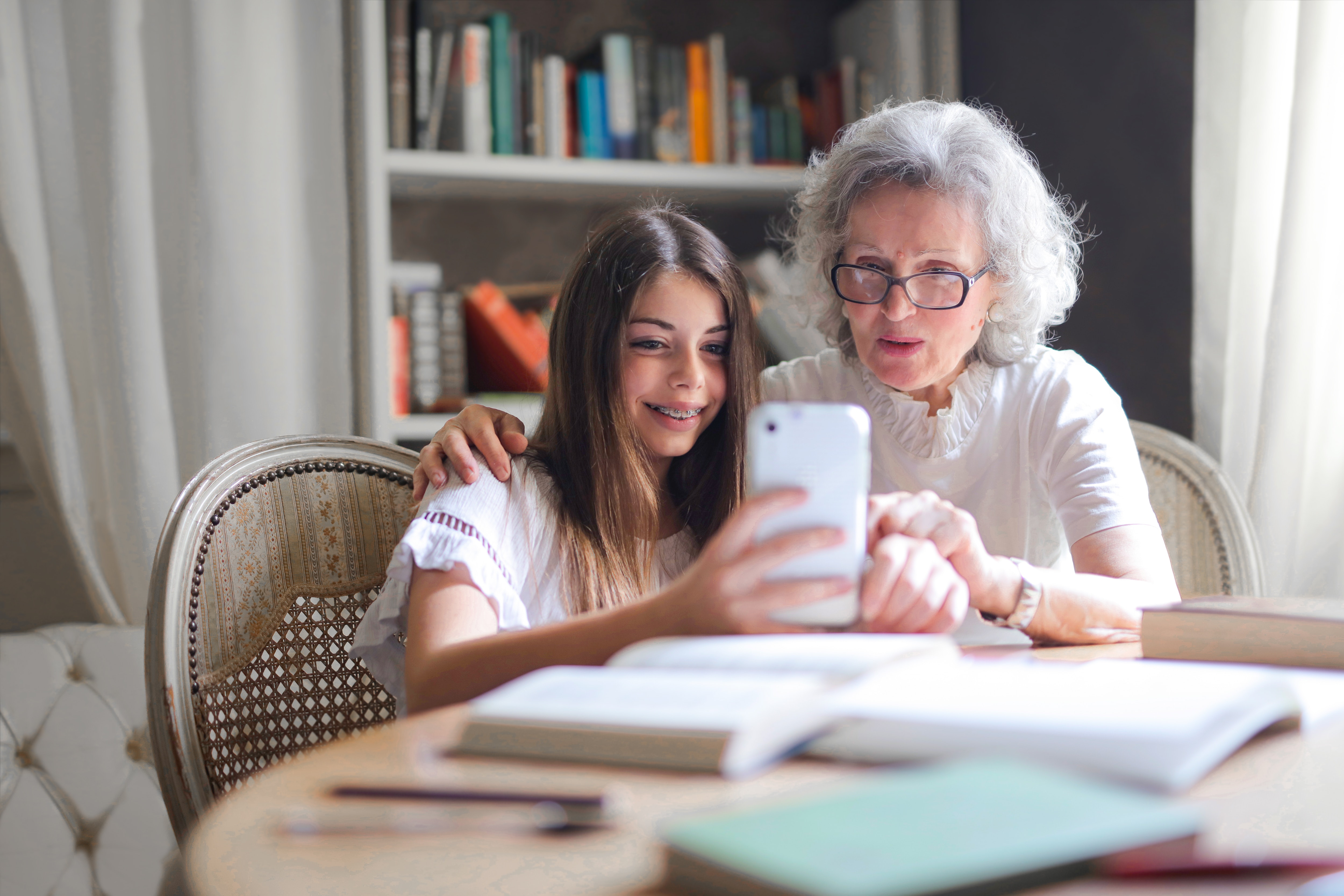 Grandchild helping her grandmother with her phone