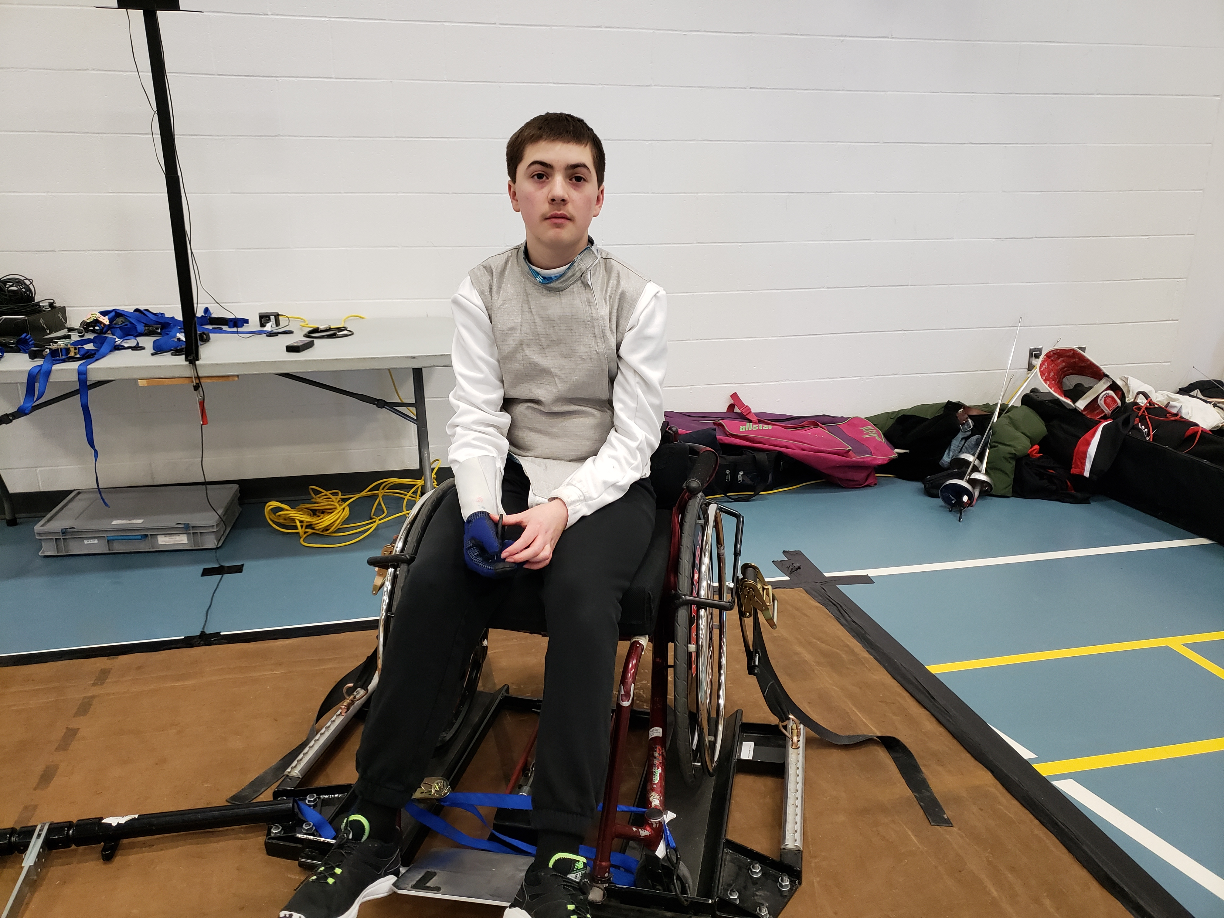 Kai in his fencing gear and his altered wheelchair