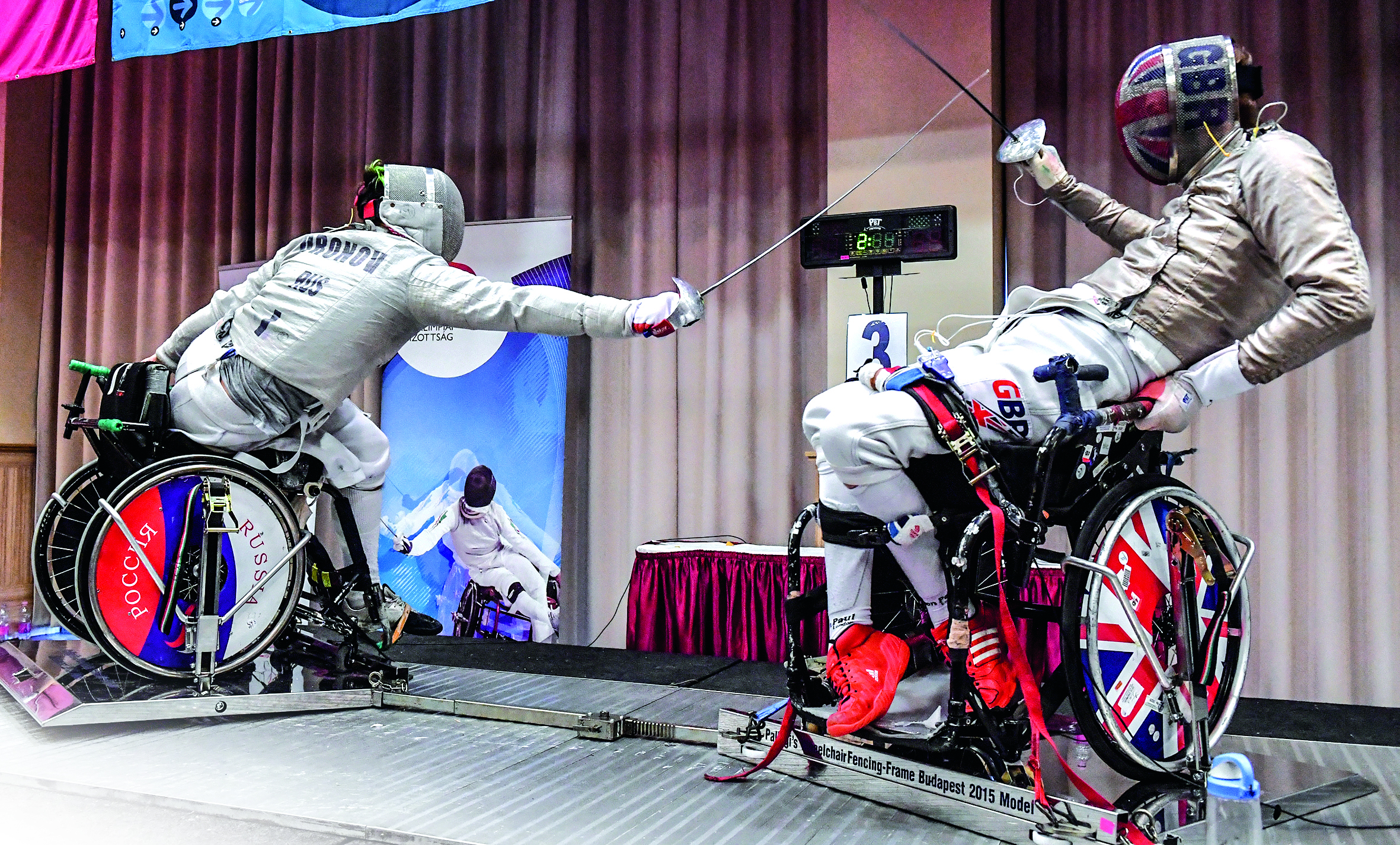Two boys in fencing gear and modified wheelchair facing each other