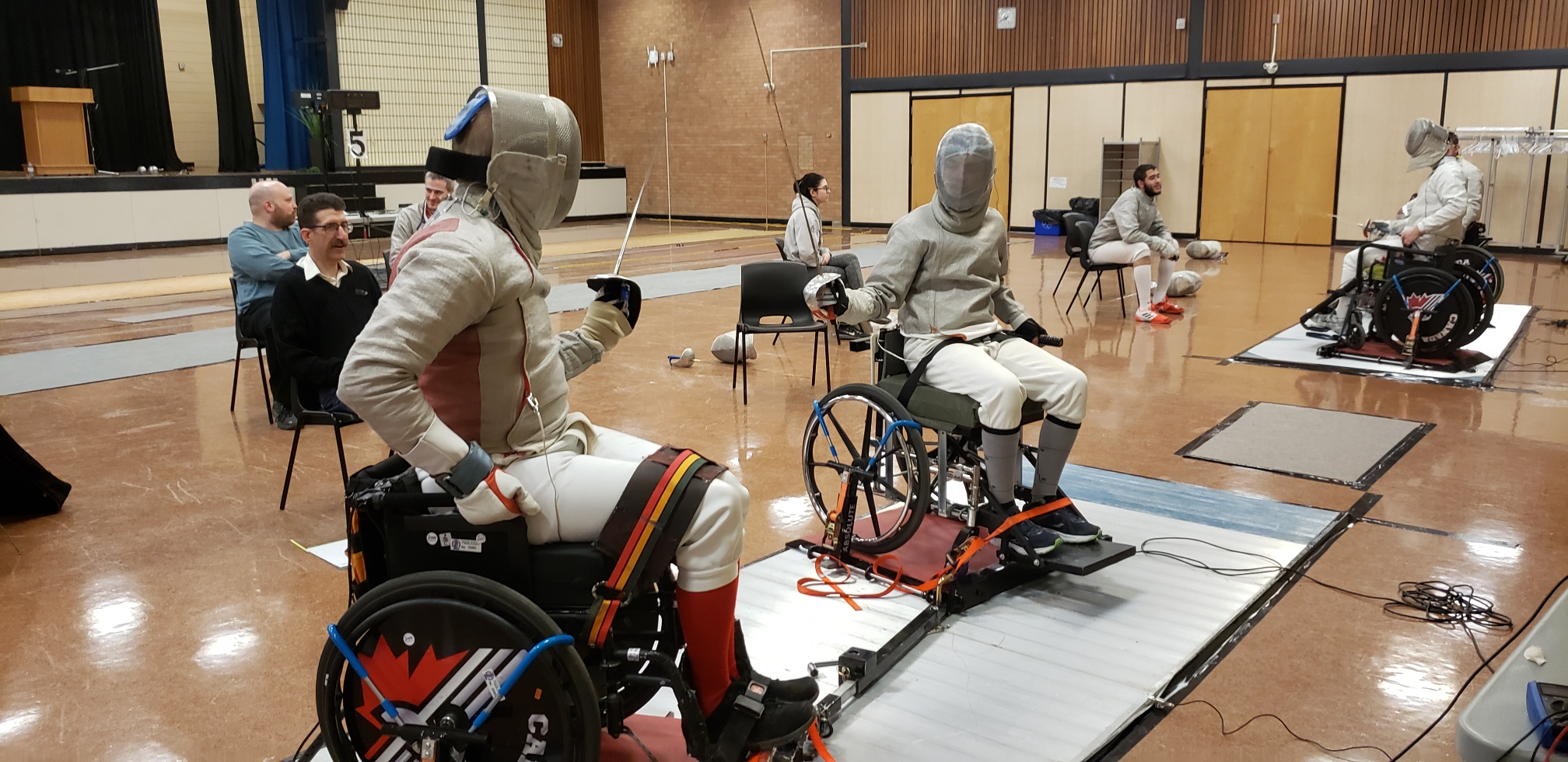 two people fencing in wheelchairs facing each other
