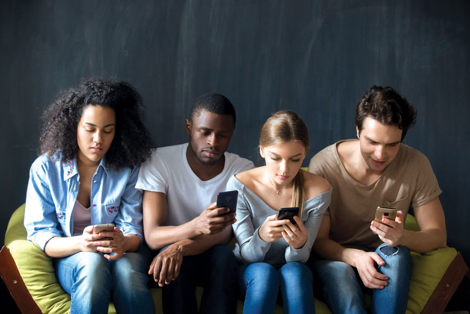 group of young adults sitting on a yellow couch on their cell phones