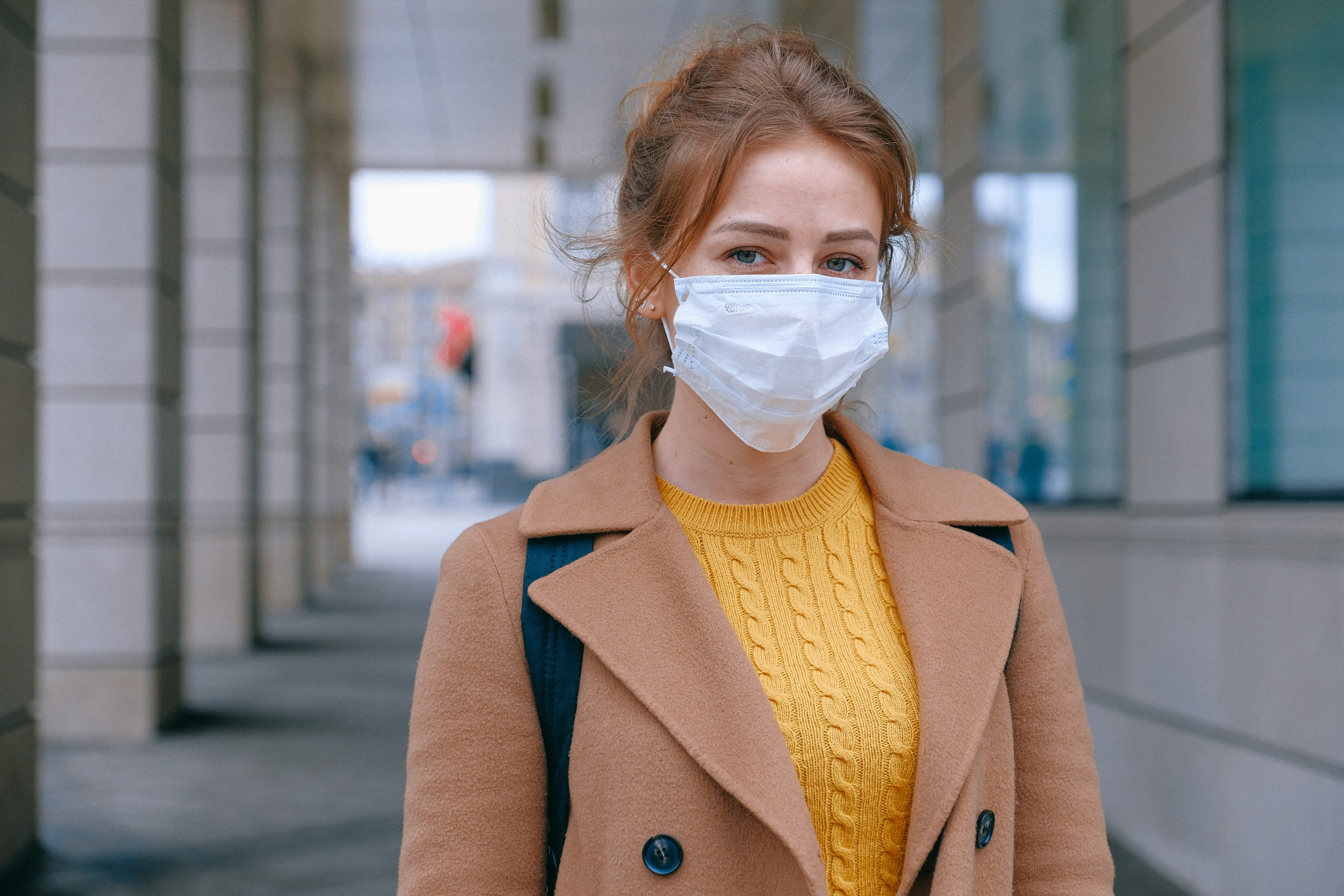 girl with light brown hair and a yellow top wearing a white mask
