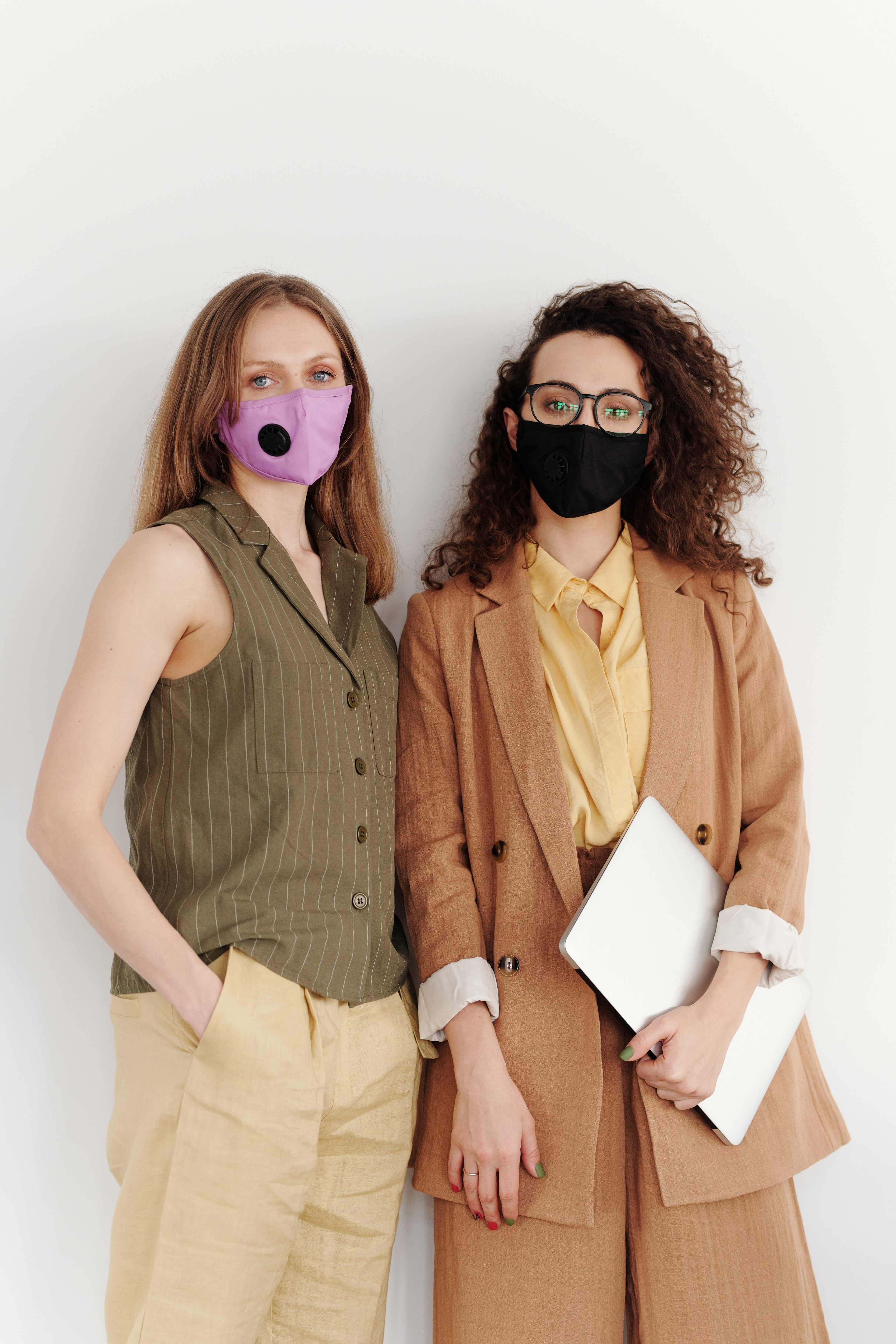two women wearing suits, one with a purple mask and one with a black mask