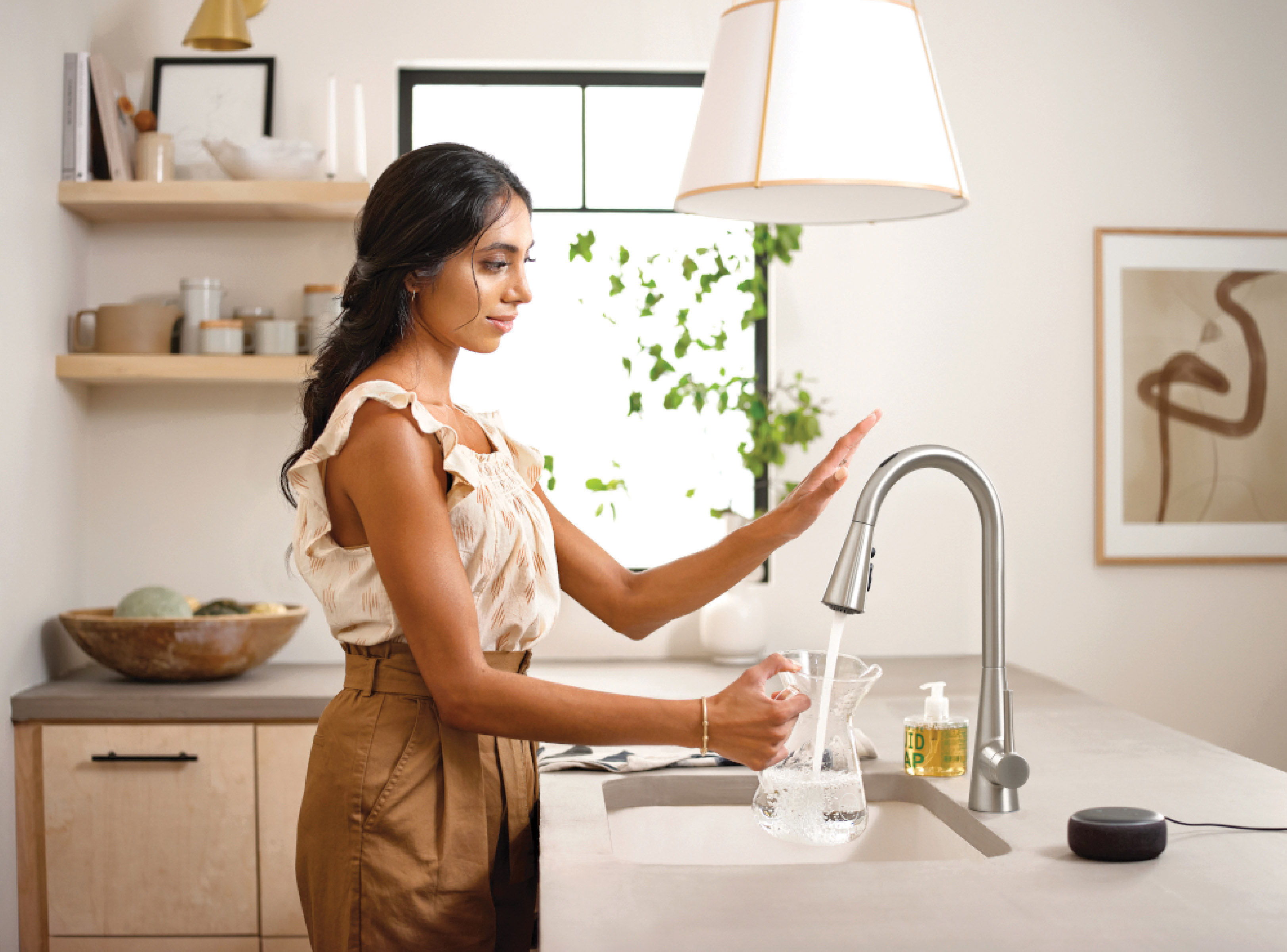 woman filling up a jug with water at her kitchen sink