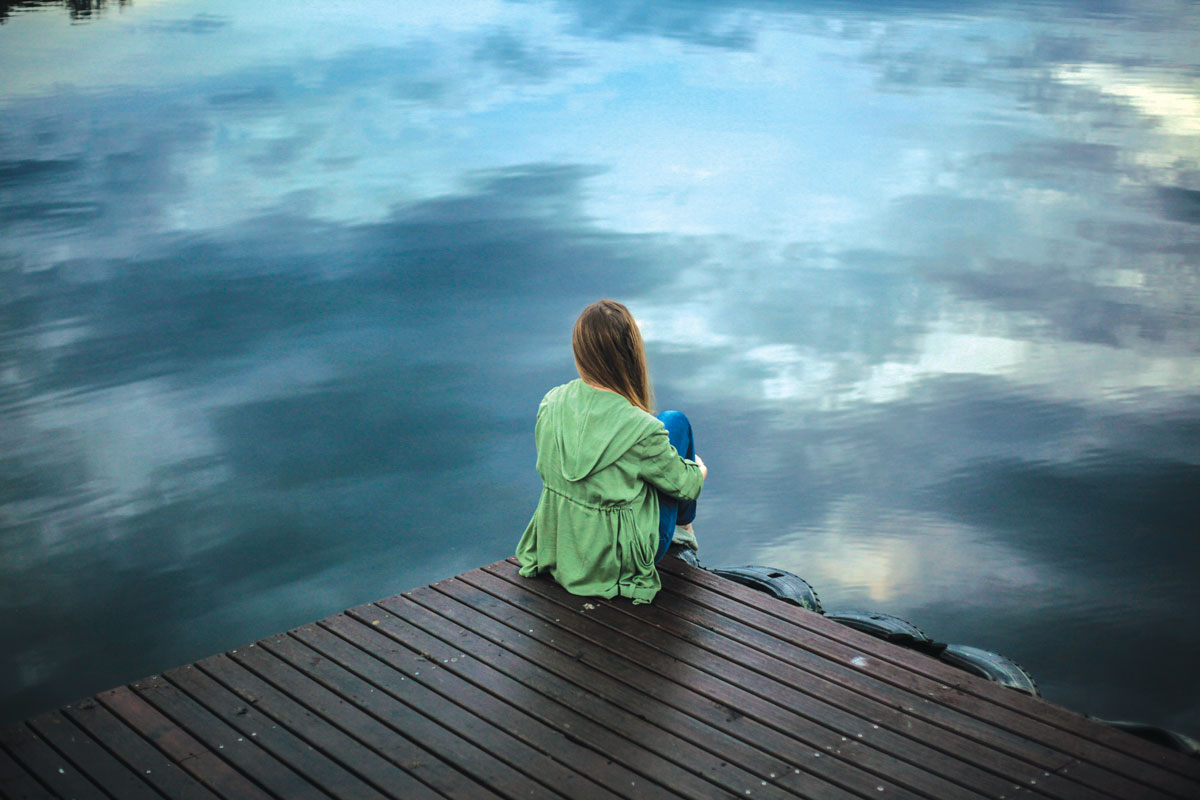 Woman sitting in front of a lake on a dock