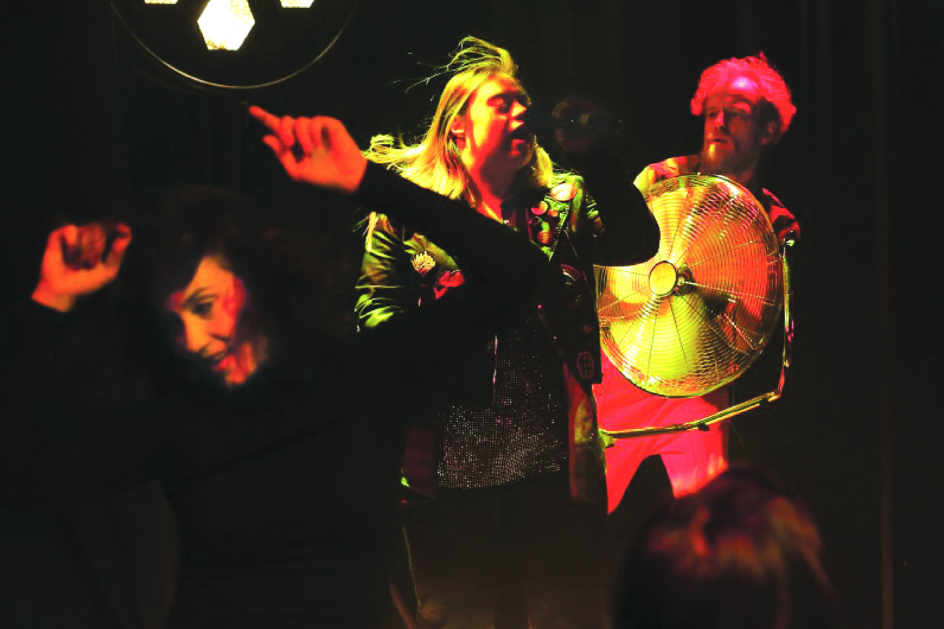Female singing with people dancing around her in a dark room