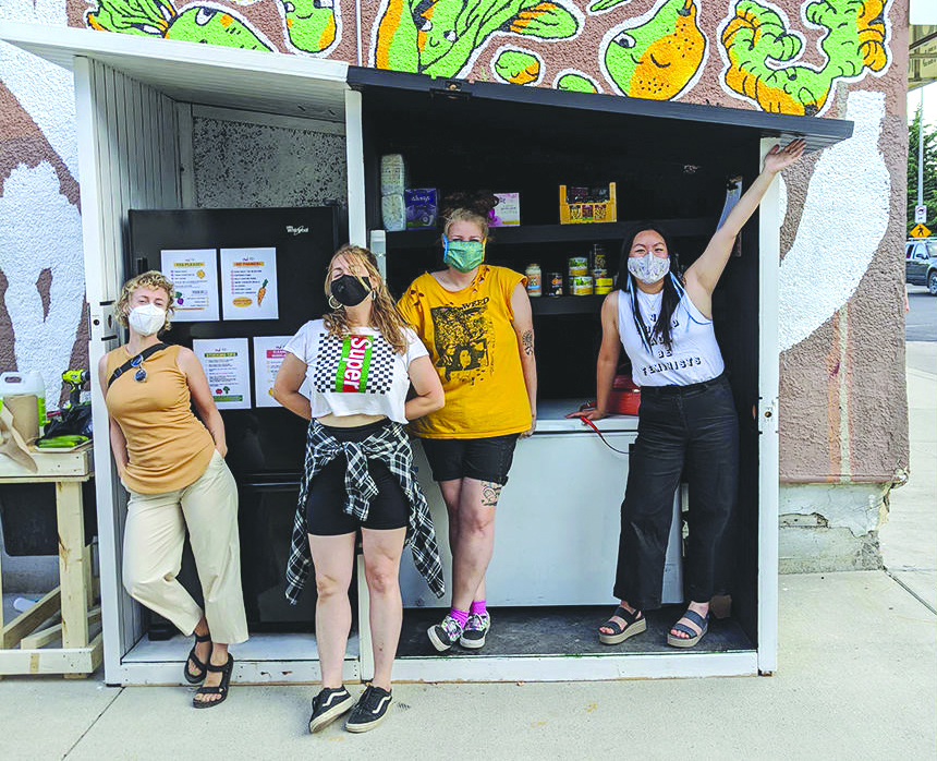 4 workers in masks standing in front of a food stall
